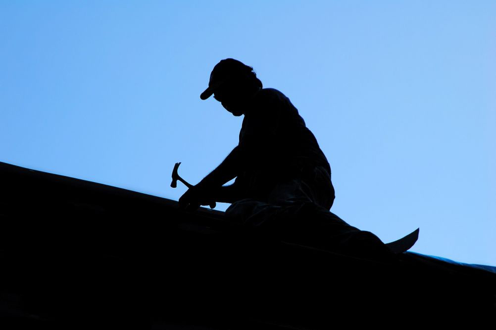 picture of man on roof with hammer